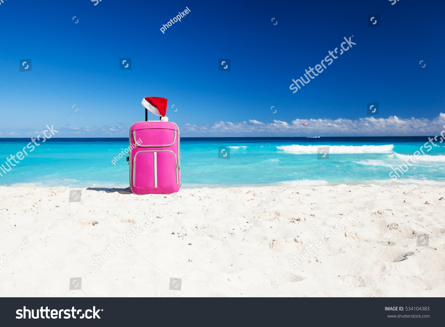 Christmas Santa Claus red hat on handle travel luggage with tropical beach and turquoise sea background New Year holidays concept