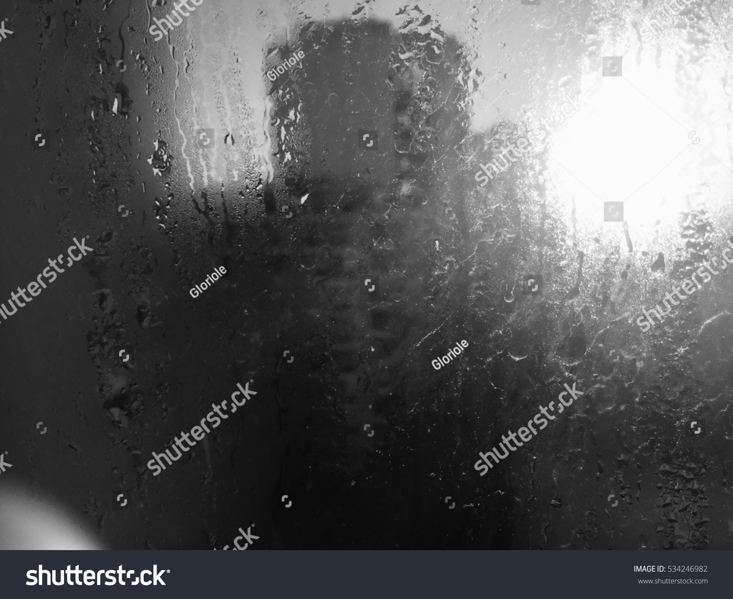 Raindrops on silver glass surface. Natural Pattern of rain drops on wet window monochrome #534246982
