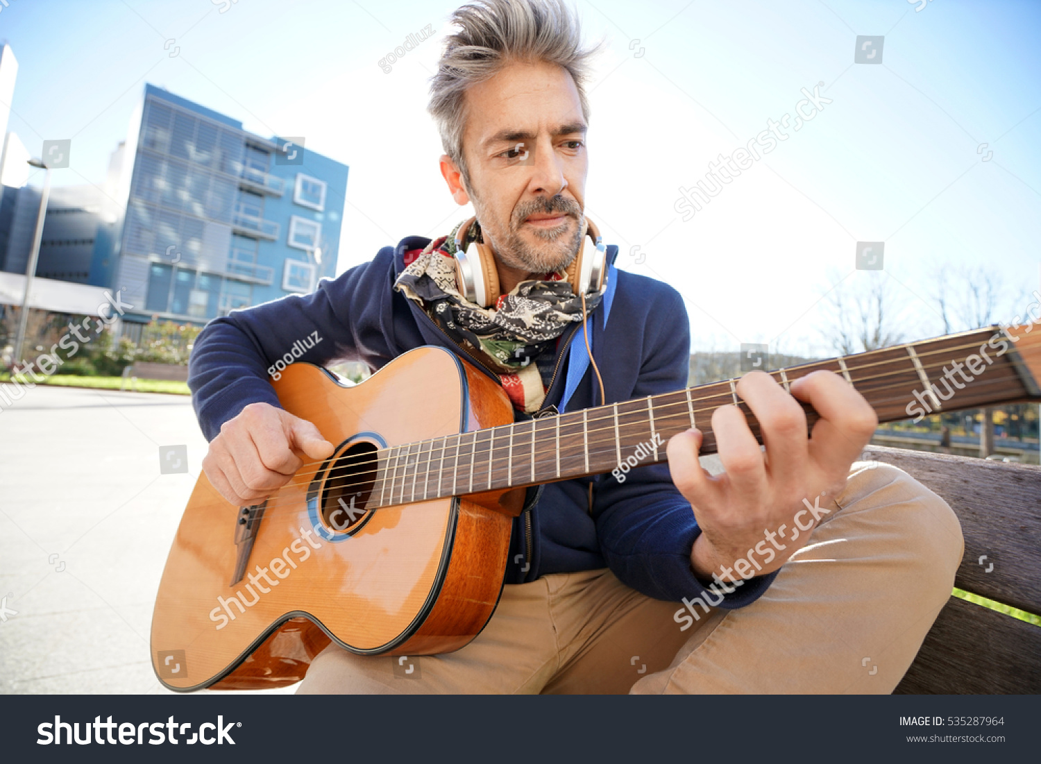 mature trendy guy playing guitar street stock photo 535287964