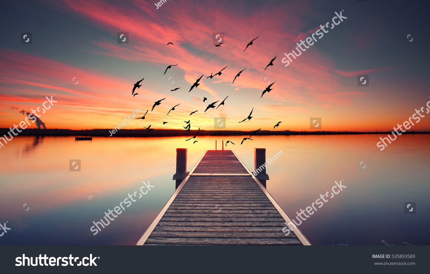 Perspective view of a wooden pier on the pond at sunset with perfectly specular reflection #535893589