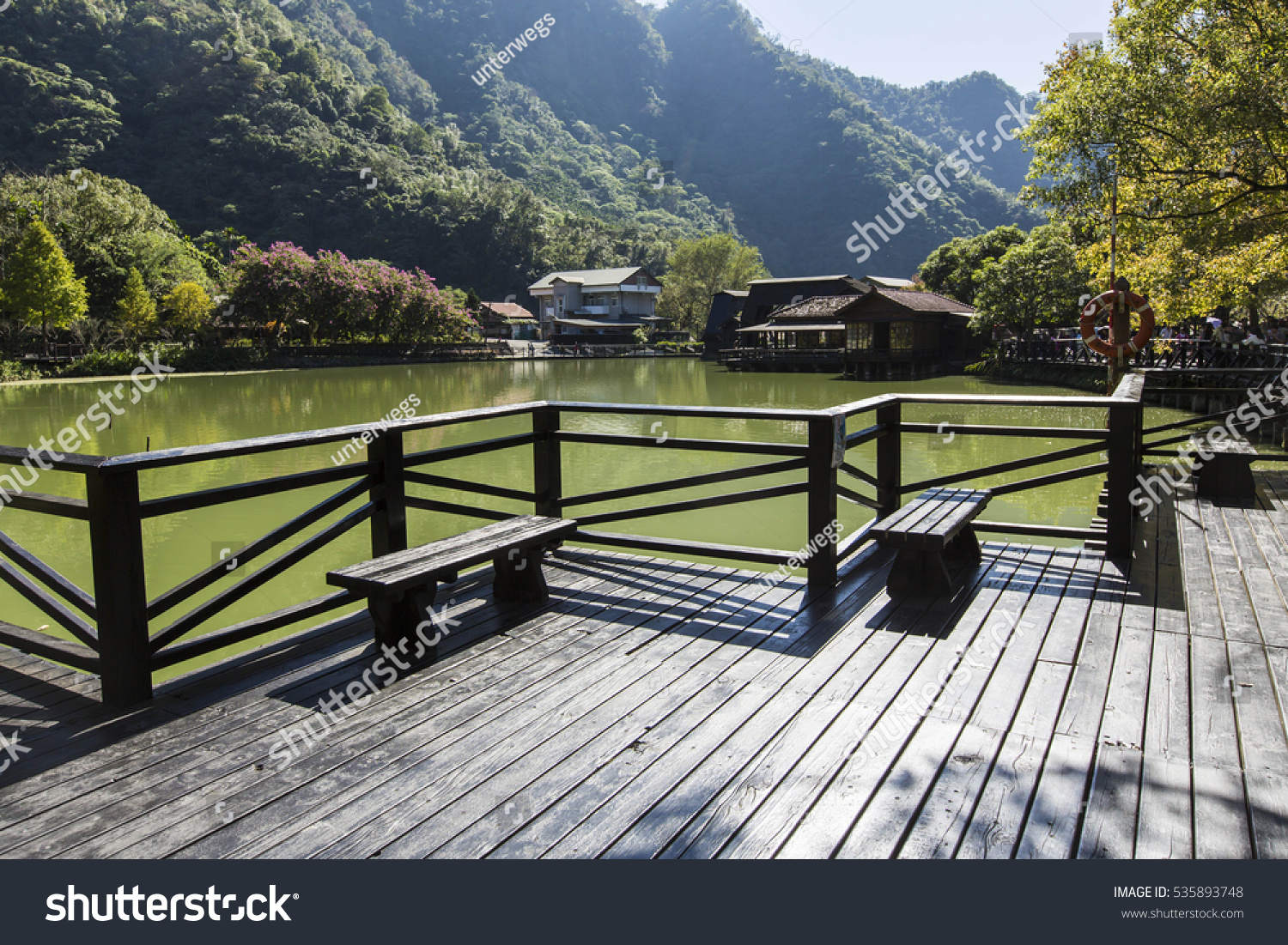 wooden benches at a lake #535893748