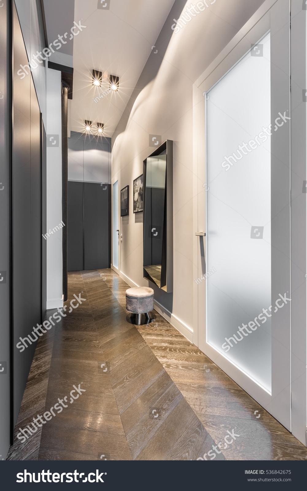 Home corridor with black wardrobe and wooden floor