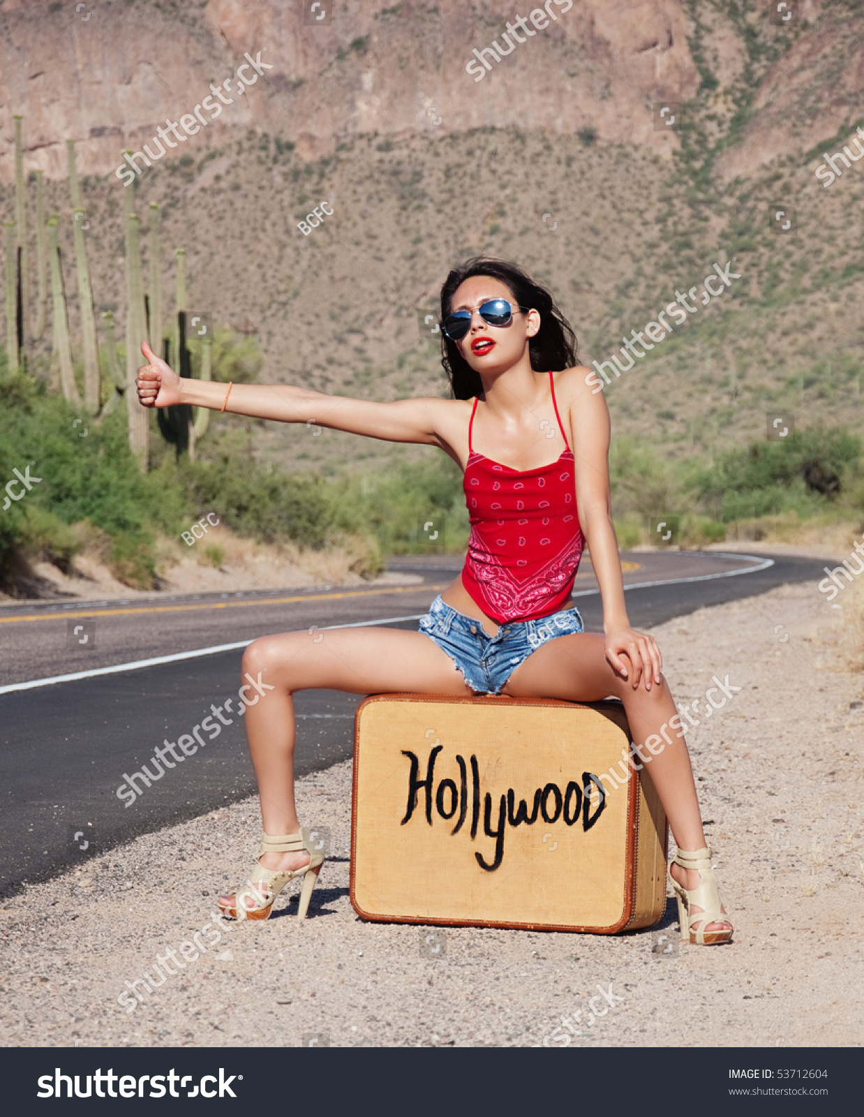 cd0e2c78a1d952 Beautiful young woman wearing red top and tiny denim shorts thumbing and  hitch hiking a ride to Hollywood, California.