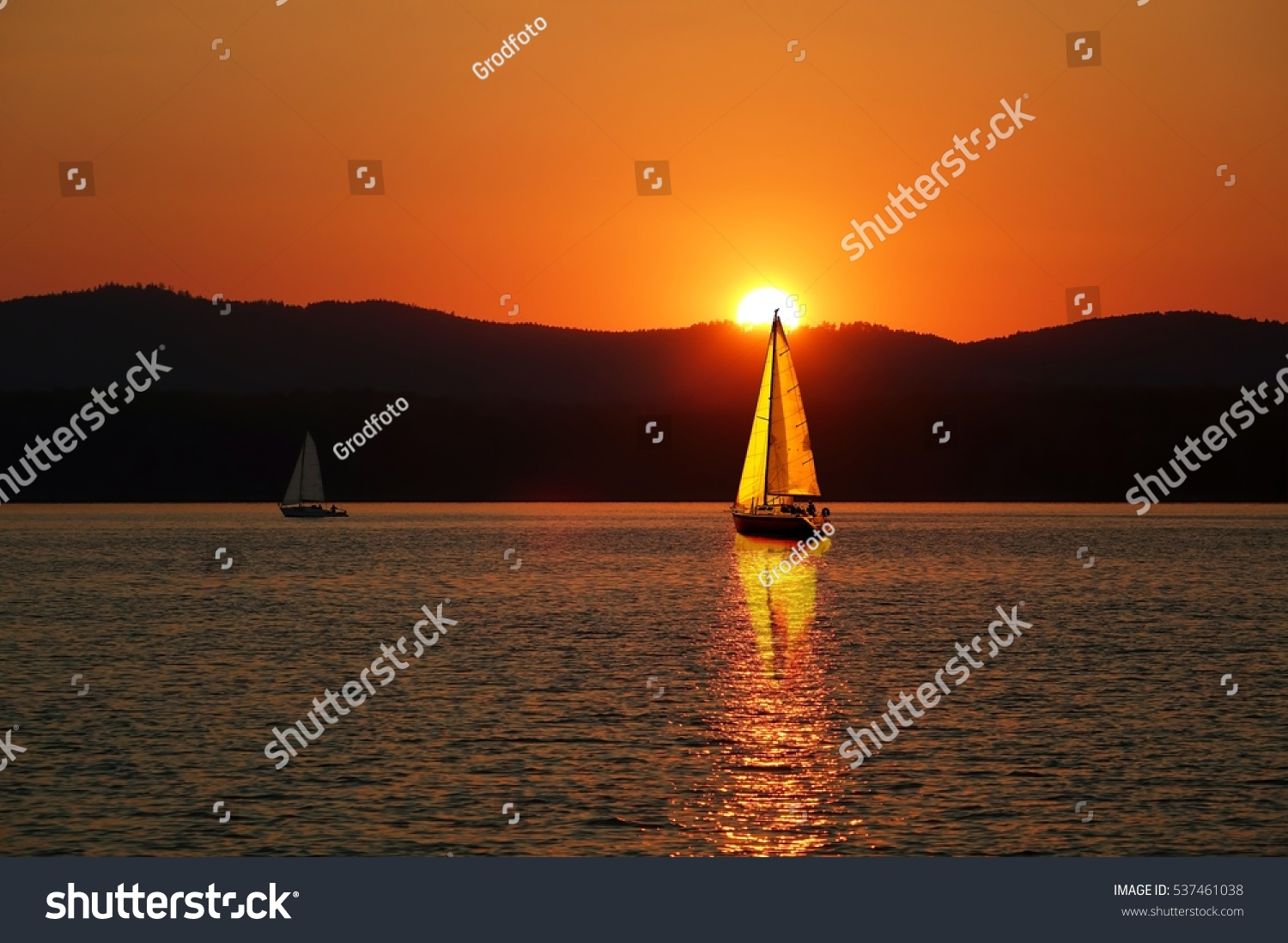 Sailboats on the beautiful Lake of the Southern Urals.Sailboat in the sunset.Reserved places at the Gold Lake South Urals