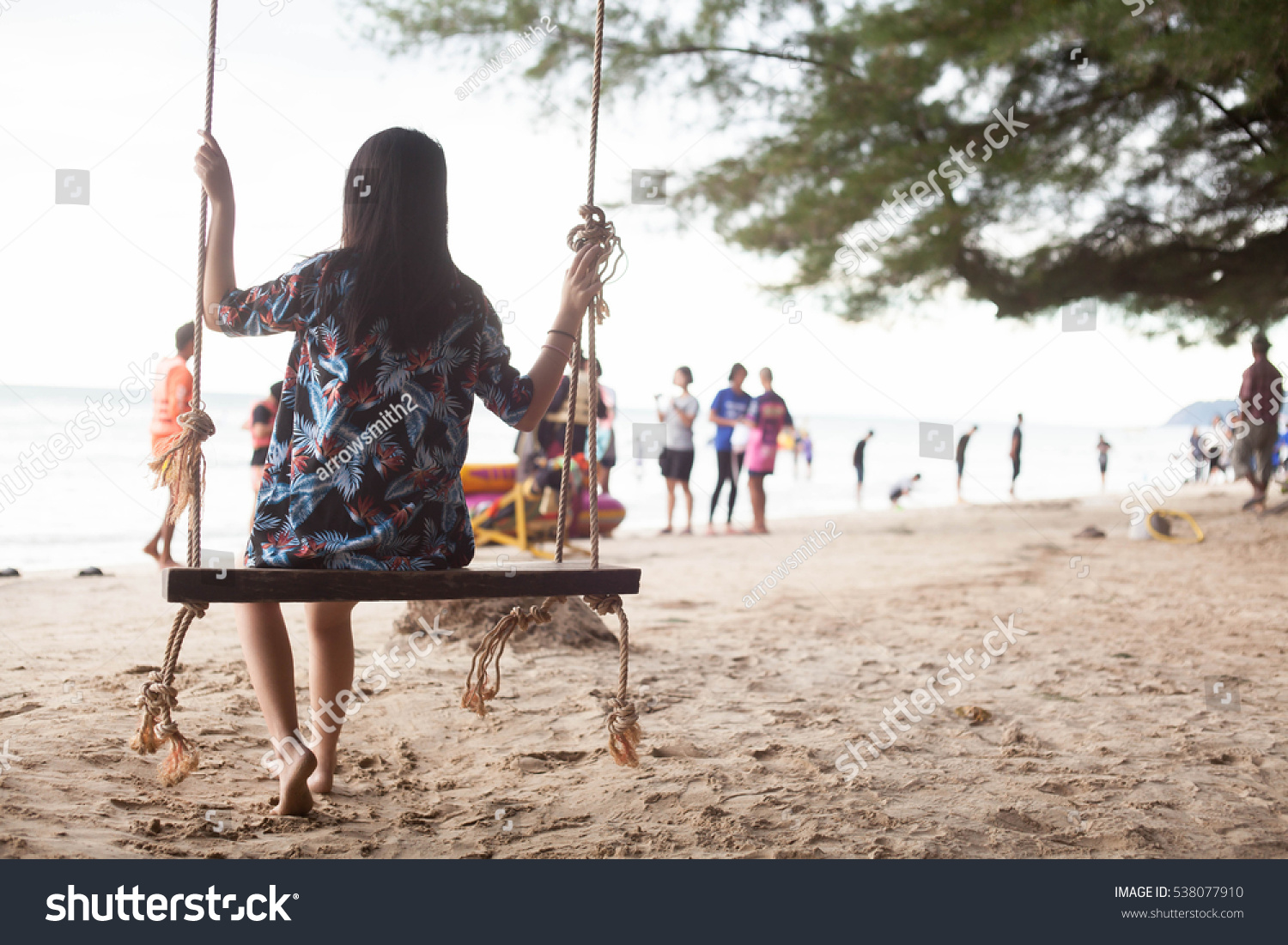 Single girl alone while swinging on the beach.