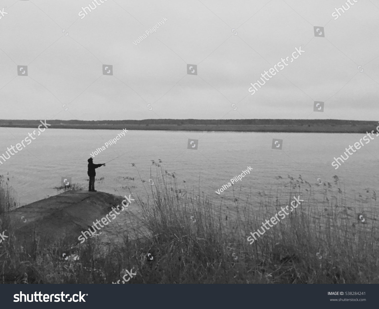 Fisherman catching fish near river evening stock photo for Where to get a fishing license near me