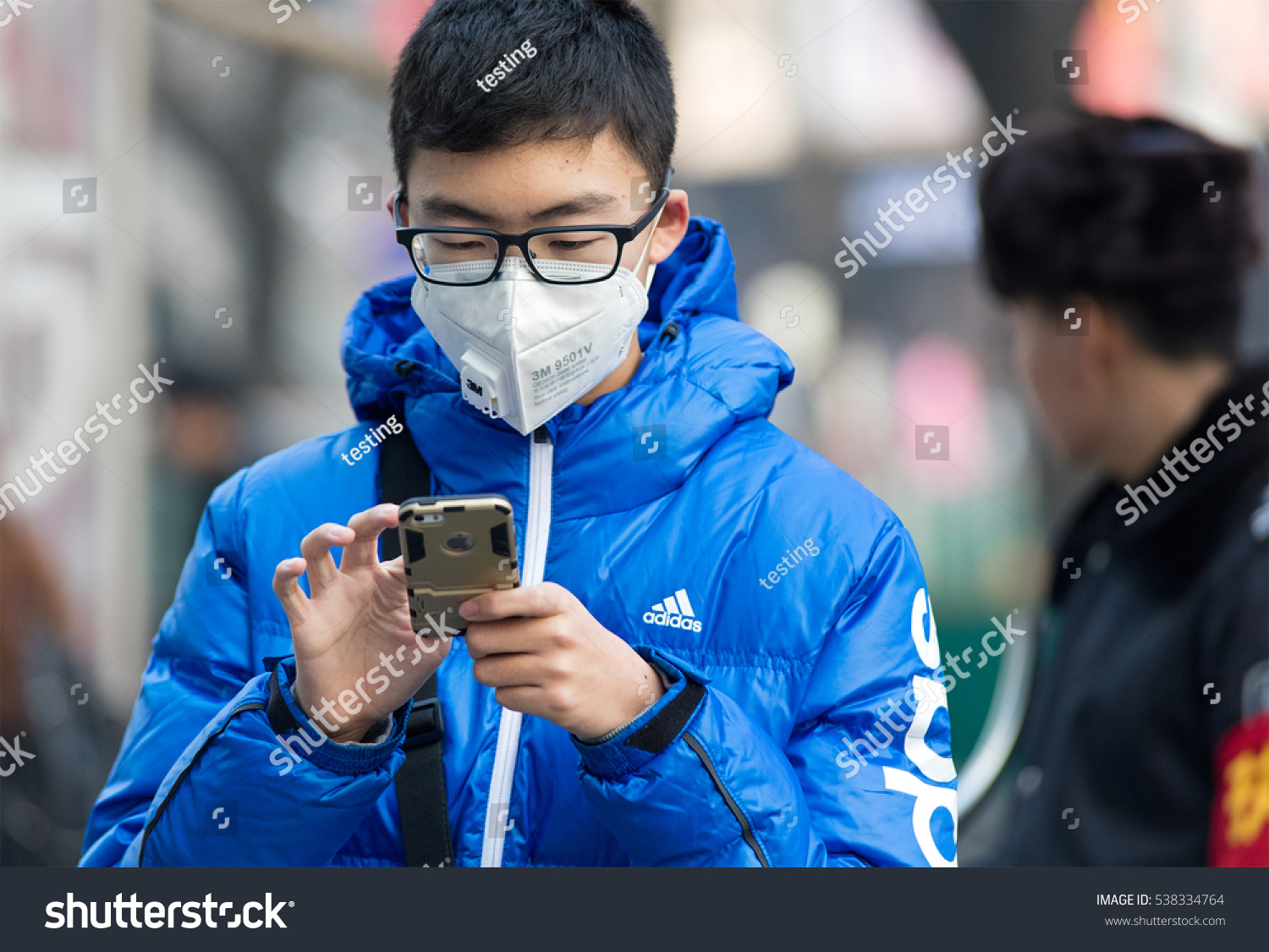 BEIJING CHINA DECEMBER 10 2016 Unidentified man wearing a facemask is seen at city downtown Beijing municipal government issued the first red alert for air pollution of this year