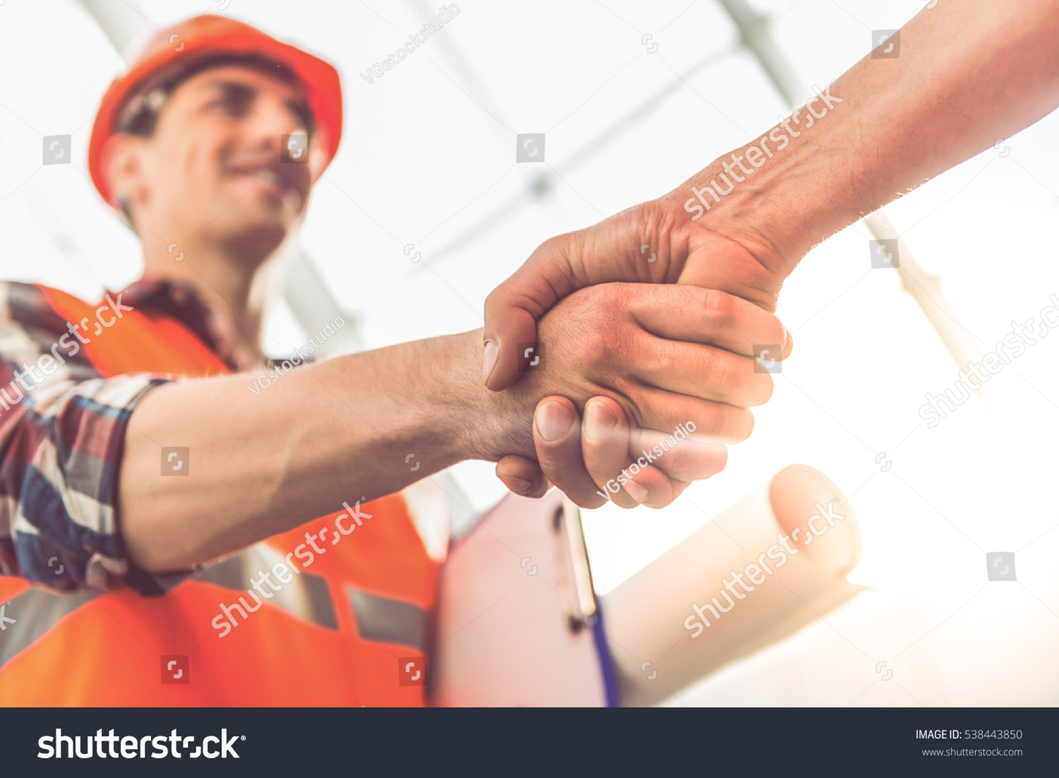 Handsome construction workers in protective helmets and vests are shaking hands while working in the office center #538443850