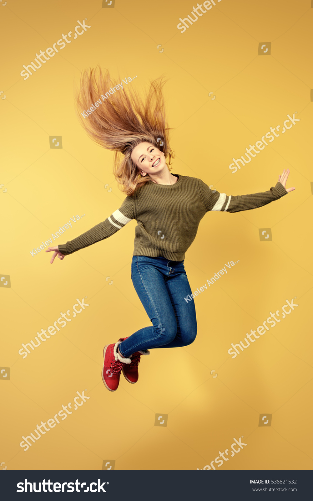 Joyful teen girl jumping over yellow background. Happiness, activity and child concept. Copy space.