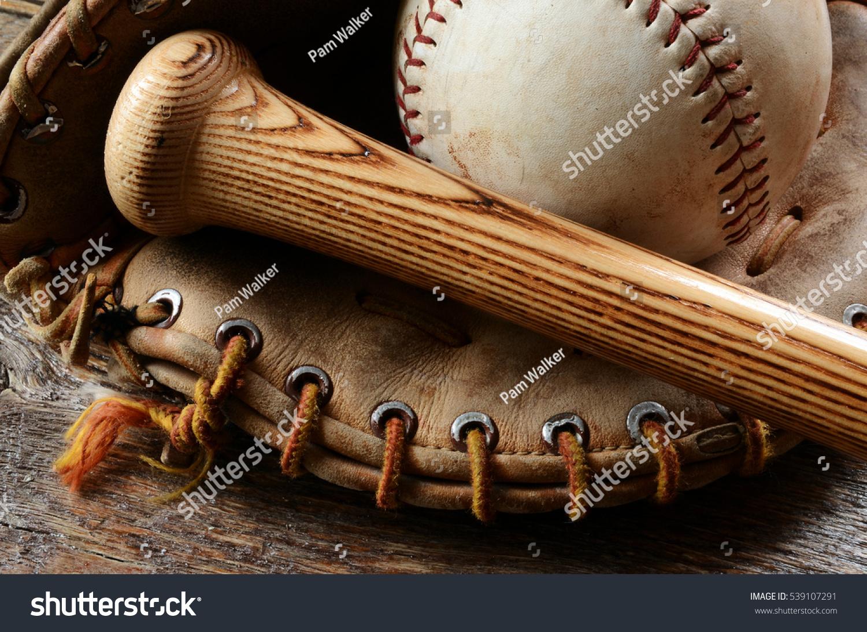 A close up image of an old used baseball, baseball bat, and baseball glove. #539107291