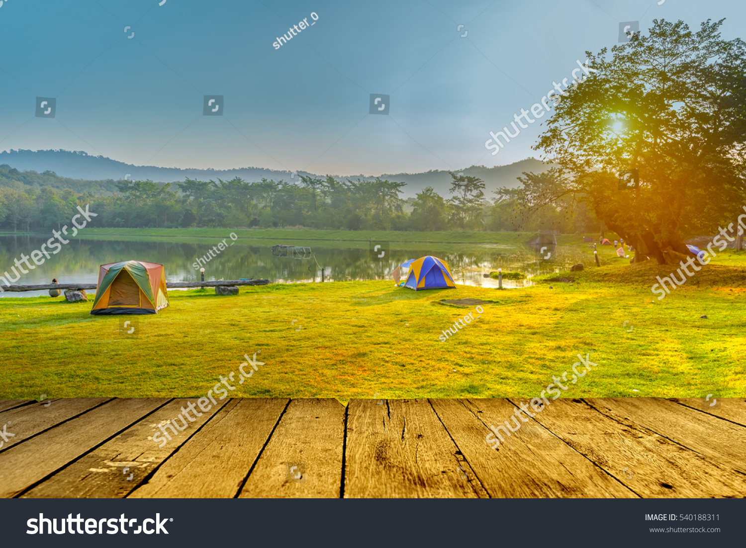Camping and tent near lake in sunrise with empty wood floor #540188311