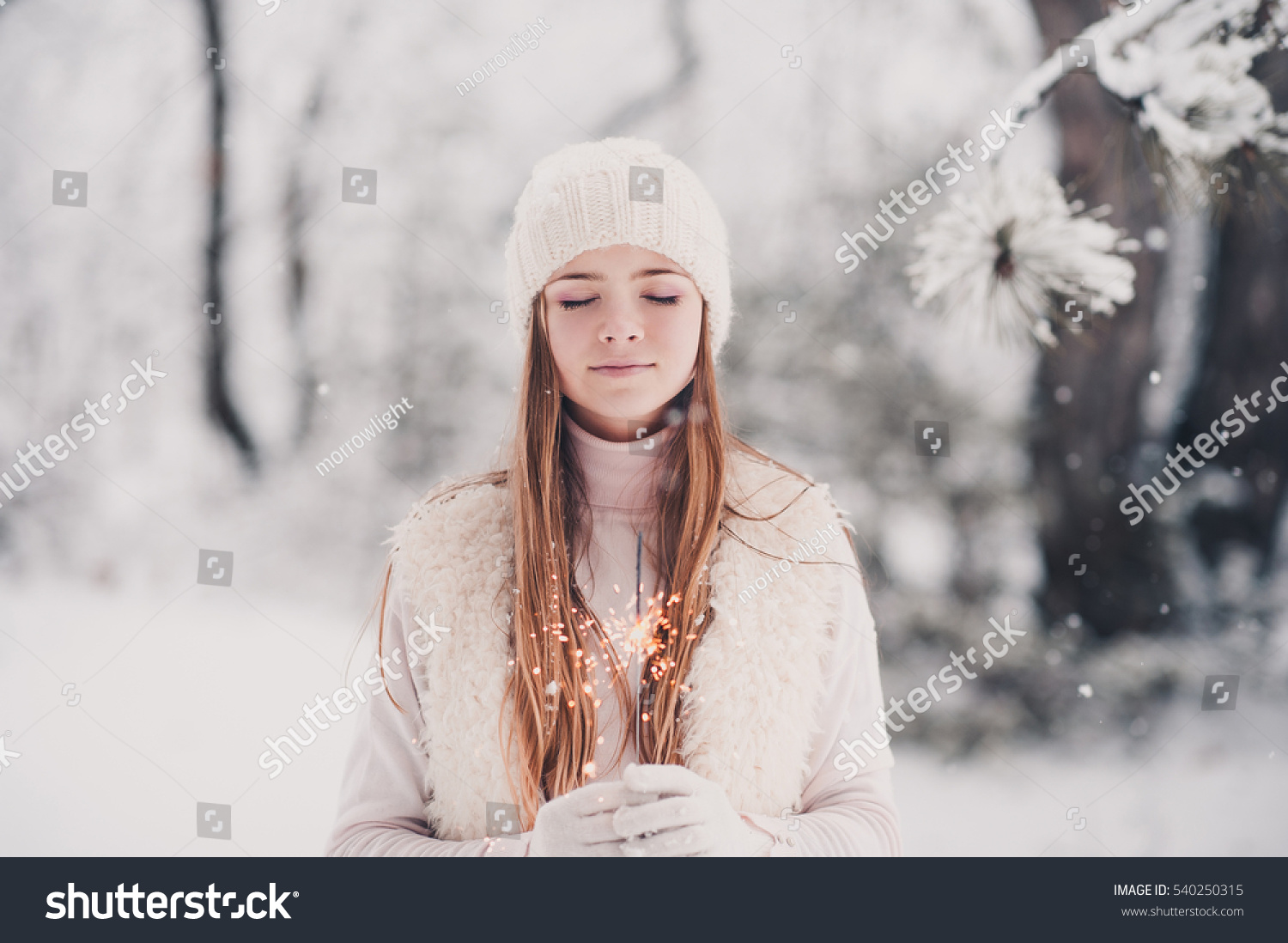 Smiling Teen Girl 14 16 Year Old Wearing Winter Knitted Clothes Holding Sparkler Outdoors Over