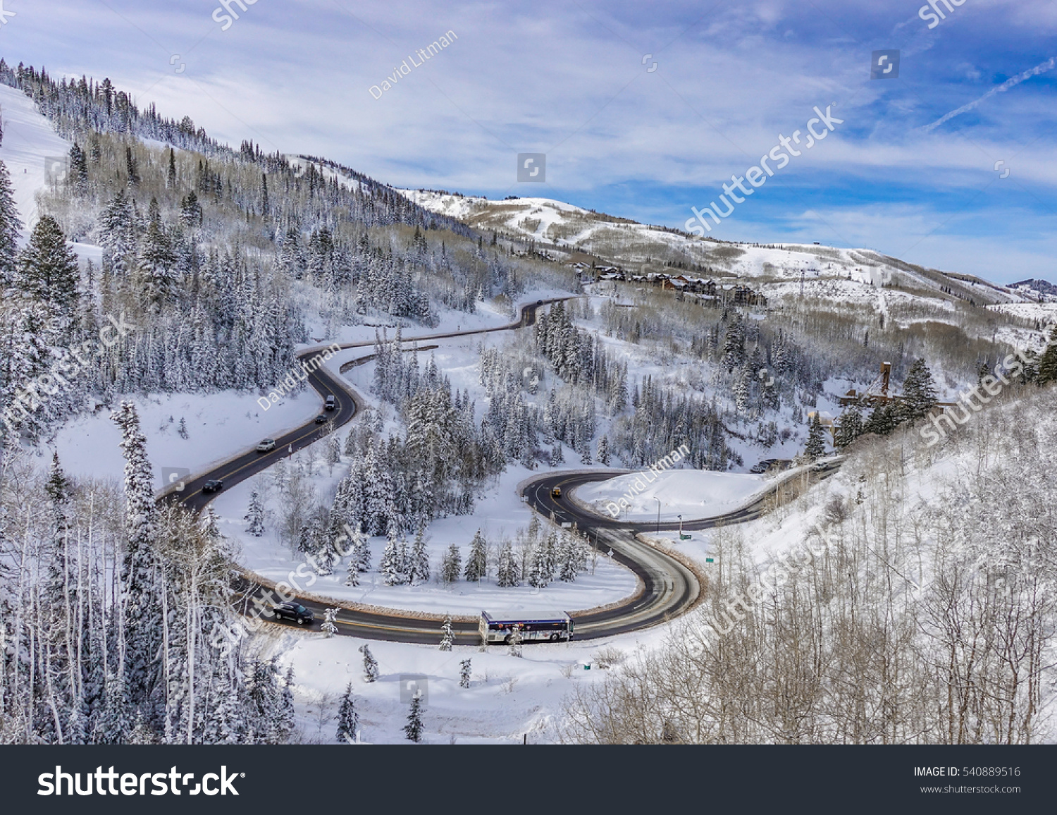 Mountain winter: The winding road to the Deer Valley Ski Resort,  host site of 2002 Winter Olympics, near Park City and The Canyons, a short drive from Salt Lake City, Utah,  with snow covered trees.