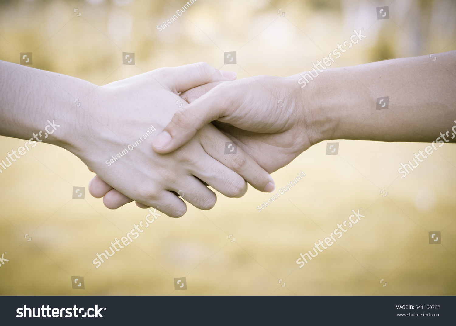 Two hands helping hand to a friend,Business man and woman shaking hands,helping hand concept and international day of peace #541160782