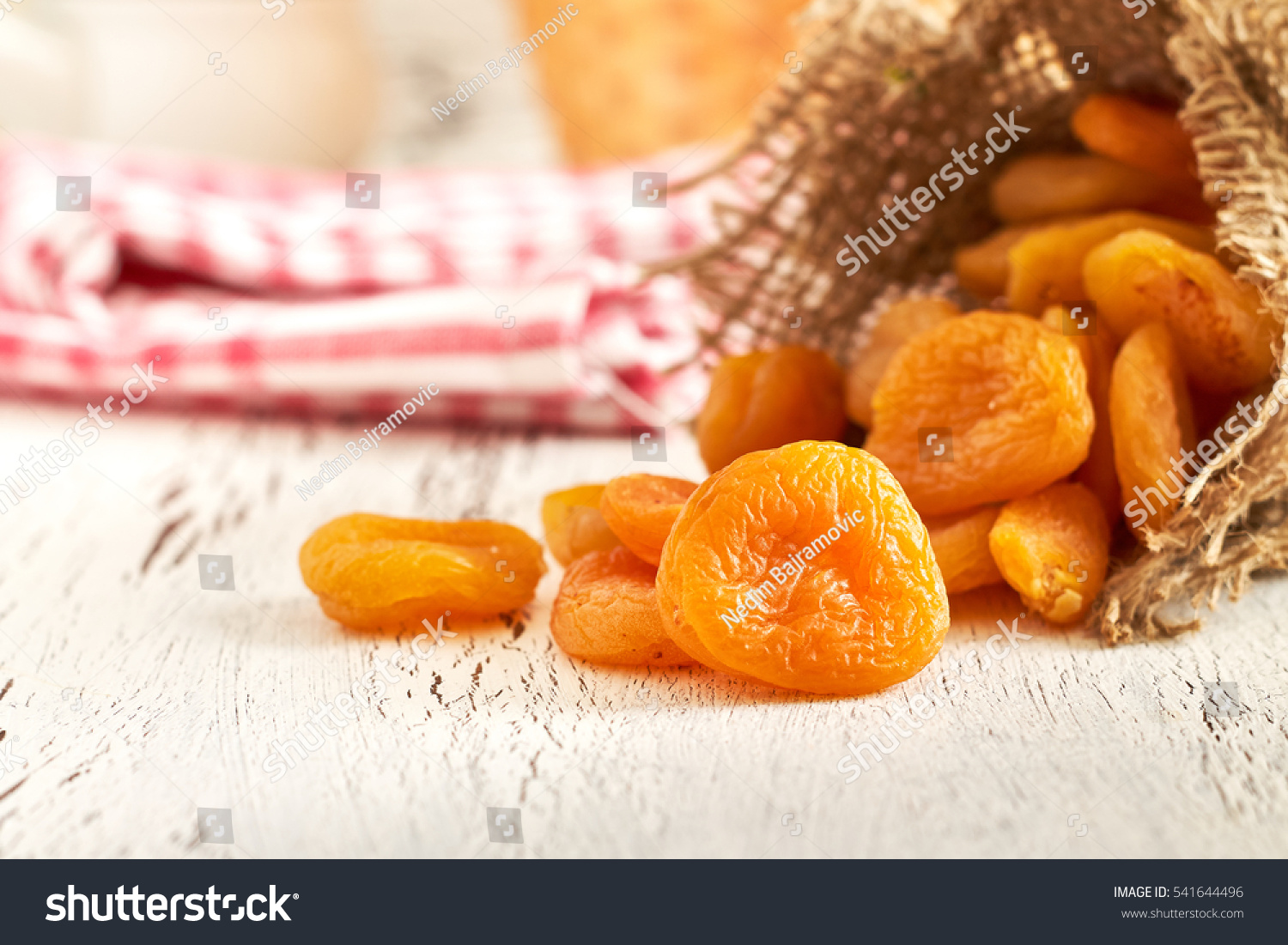 Dried apricots on white rustic wooden background #541644496