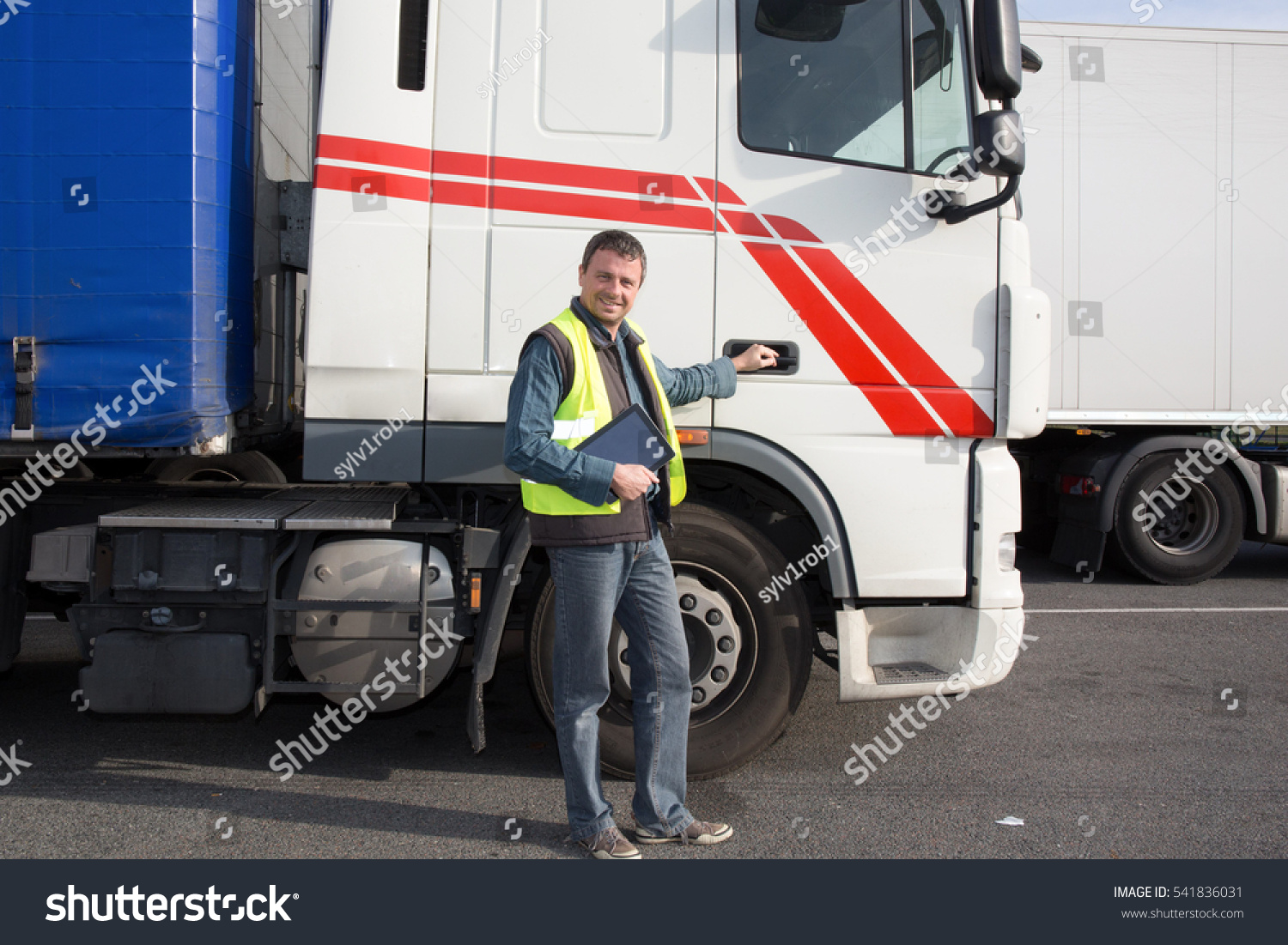 Logistics - proud driver with tablet computer, in front of trucks . #541836031