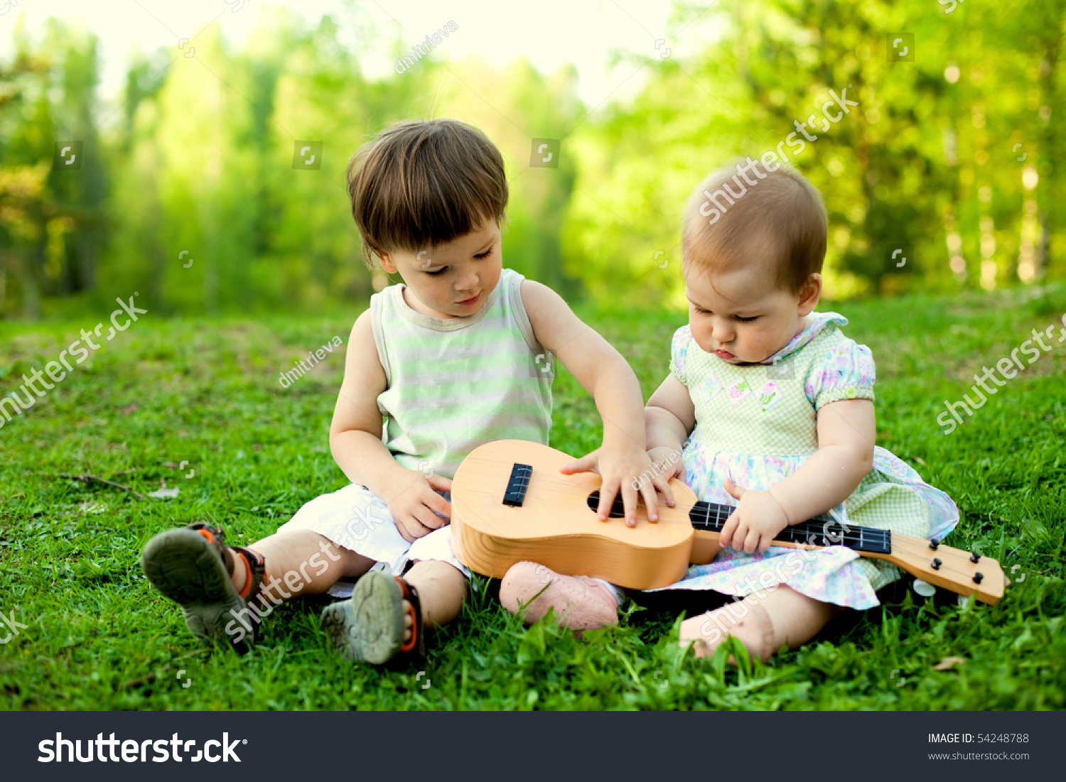 two cute children playing guitar together stock photo (edit now