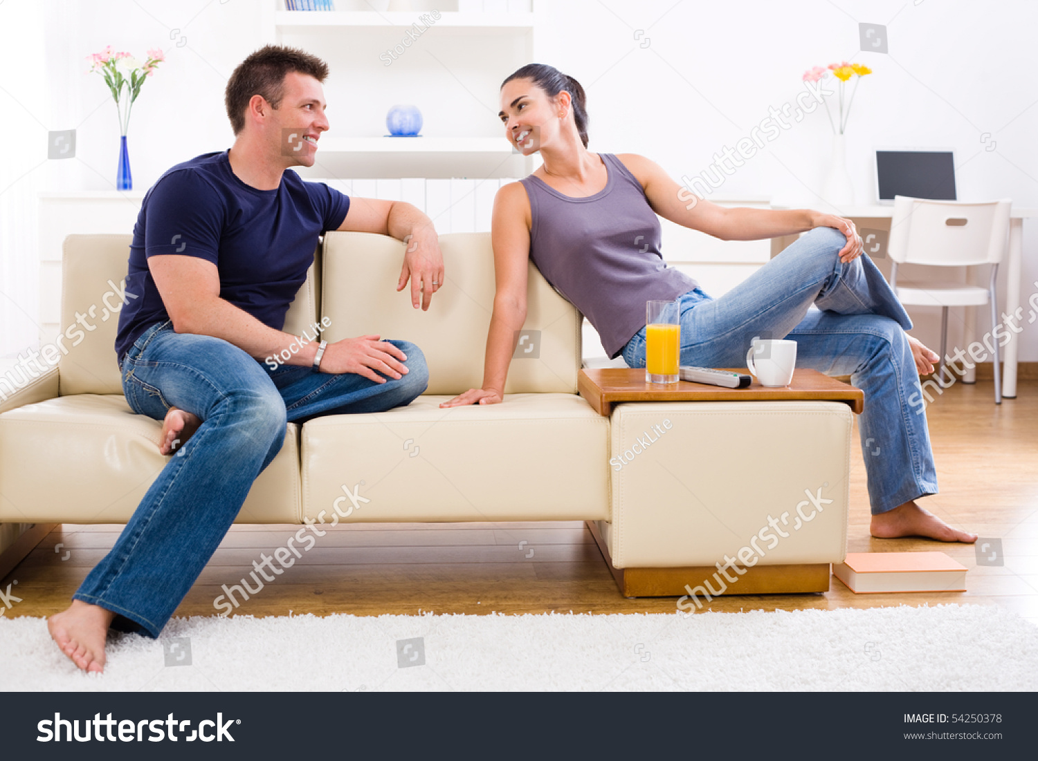happy young couple sitting on sofa at home smiling stock. Black Bedroom Furniture Sets. Home Design Ideas
