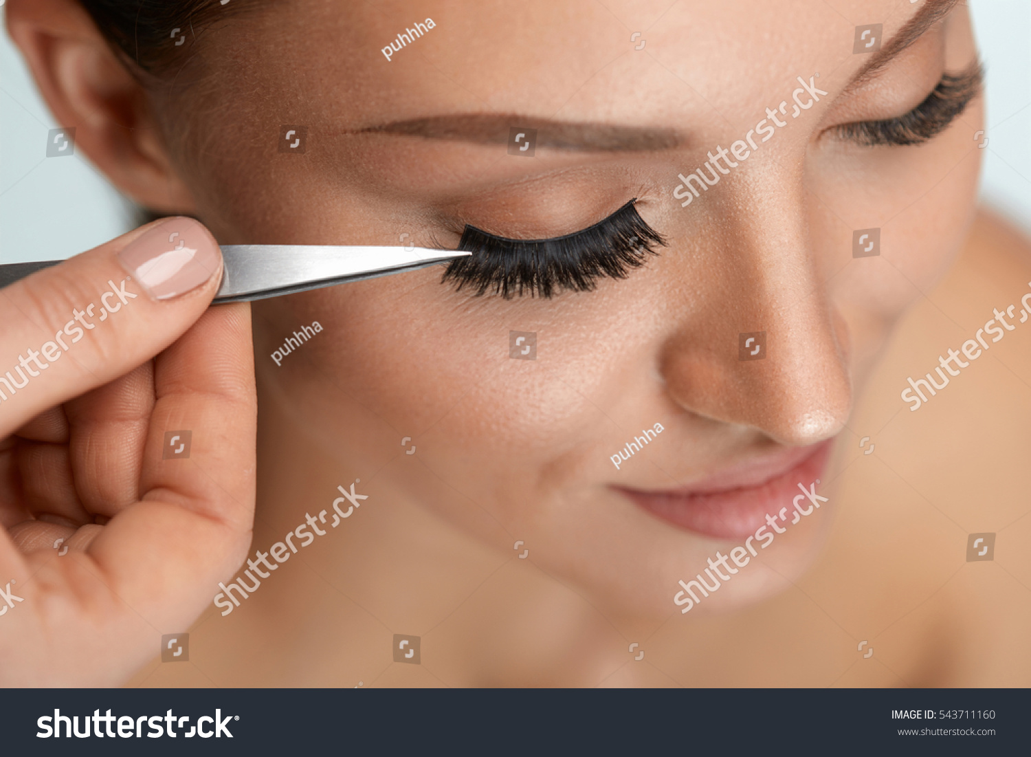 08bab5b5d72 Beautiful Woman Applying False Eyelashes With Tweezers. Closeup Of Young  Female Model Face With Professional Facial Makeup, Smooth Skin And Long  Black Thick ...