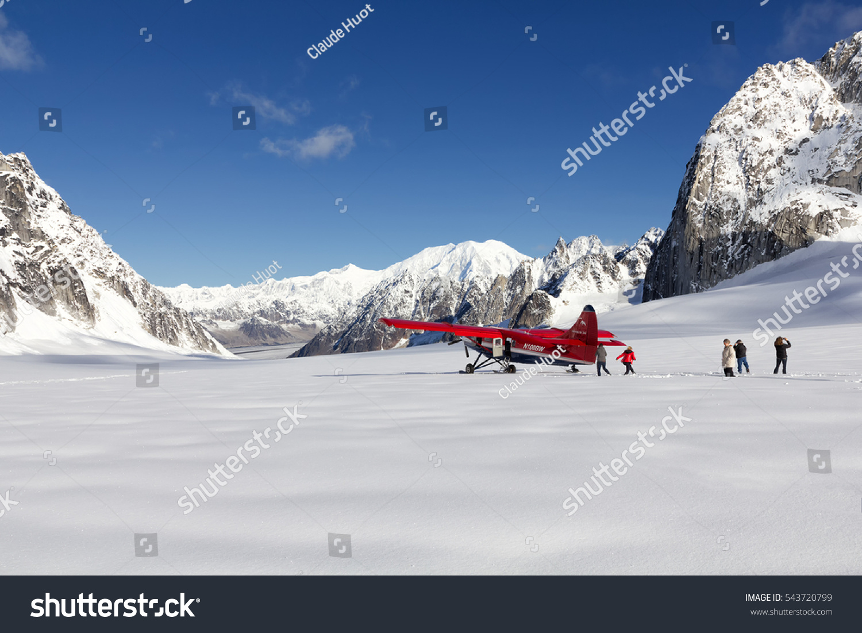 DENALI NATIONAL PARK, ALASKA, USA - SEPTEMBER 14, 2013: Tourists walk in deep snow and take pictures after plane landing on Pika Glacier in Denali National Park, Alaska near Mount McKinley