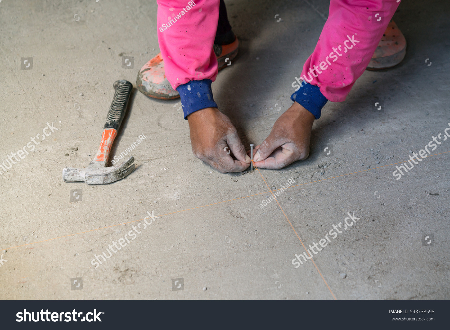 Hand hold nail hit on concrete stock photo royalty free 543738598 hand hold nail hit on concrete floor for plane laying ceramic tiles installing tiles in dailygadgetfo Gallery