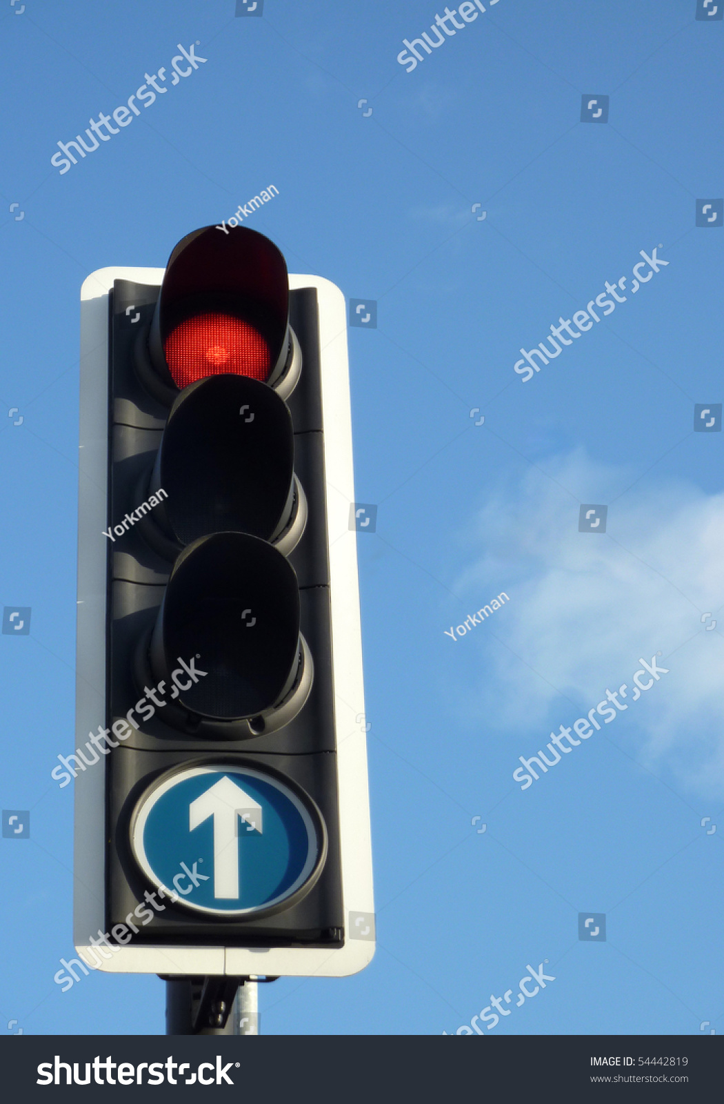 Closeup of red traffic light against blue sky