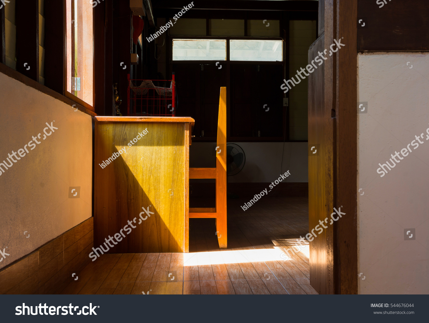 Inside house sunshine light through window passing desk chair and floor deep dark background of