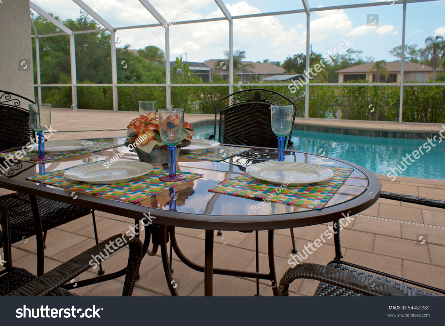 A Table Is Set For Dinner On An Outside Patio Or Lanai With Swimming Pool In