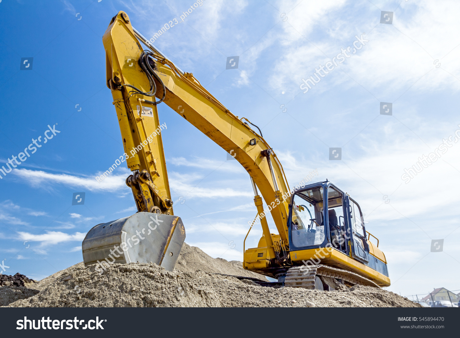 Construction Site Soil : Yellow excavator making pile soil by stock photo