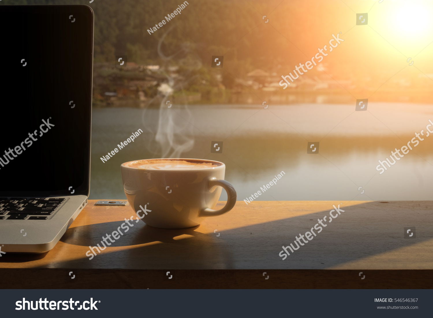 Coffee morning and laptop on wooden table with lake, mountain and village background. #546546367