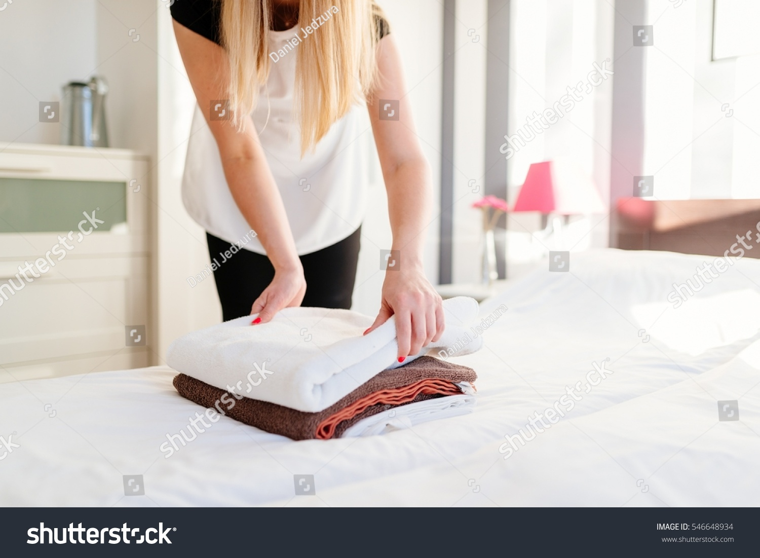 Young Hotel Maid Placing Fresh Towels Stock Photo