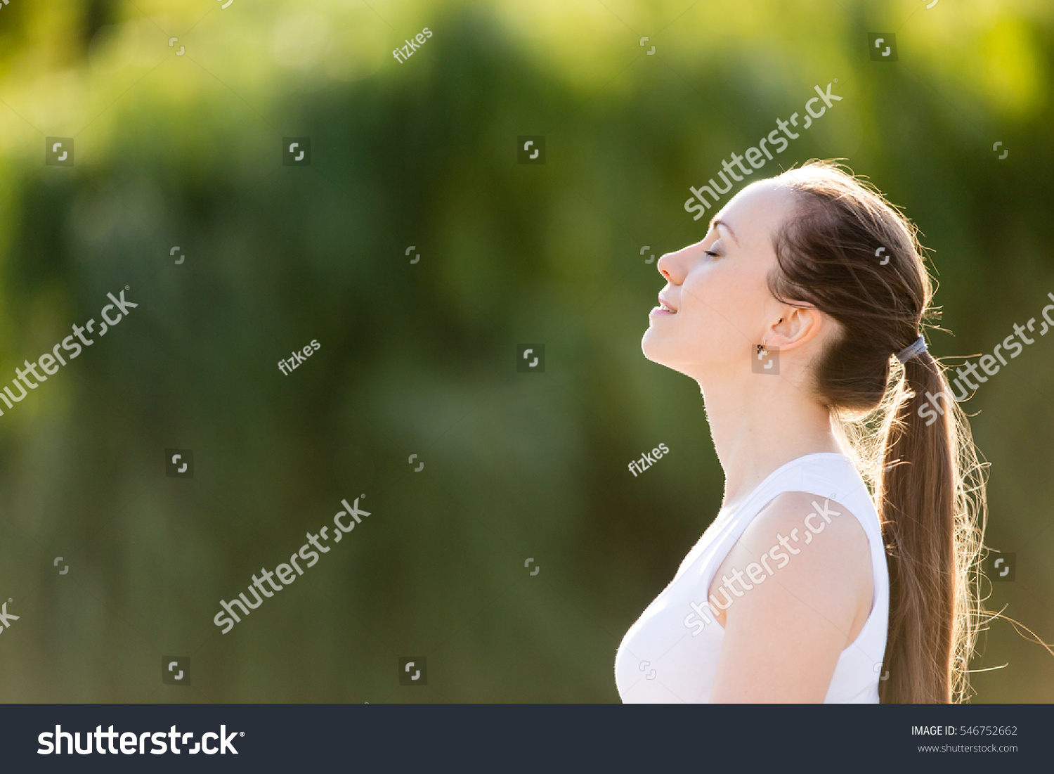 Portrait of beautiful smiling young woman enjoying yoga, relaxing, feeling alive, breathing fresh air, got freedom from work or relations, calm and dreaming with closed eyes, in green park, copy space #546752662