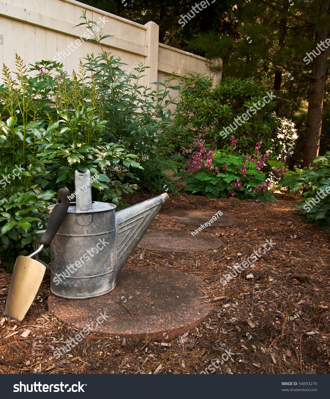 A trowel sits against an old watering can on a stone path that leads ...