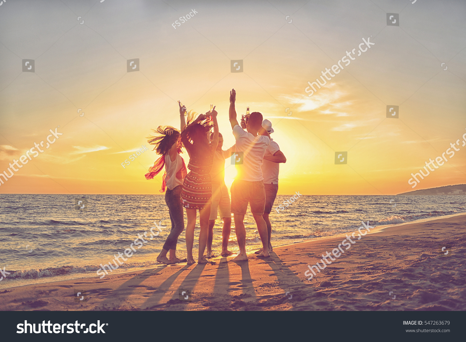 group of happy young people dancing at the beach on beautiful summer sunset #547263679