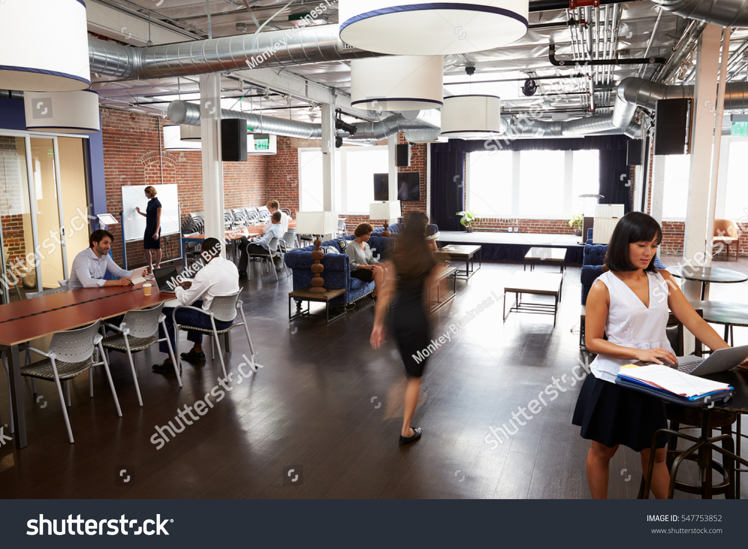 wide angle view busy design office. interior of busy design office with staff wide angle view