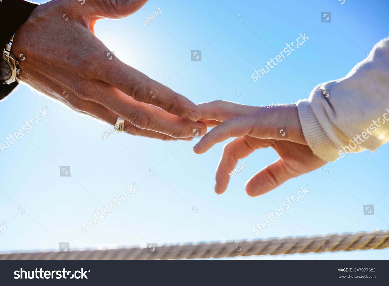Closeup on hands Back view silhouette of male and female couple on holiday travel vacation outdoors background Blue sunny sky on lovely valentines day