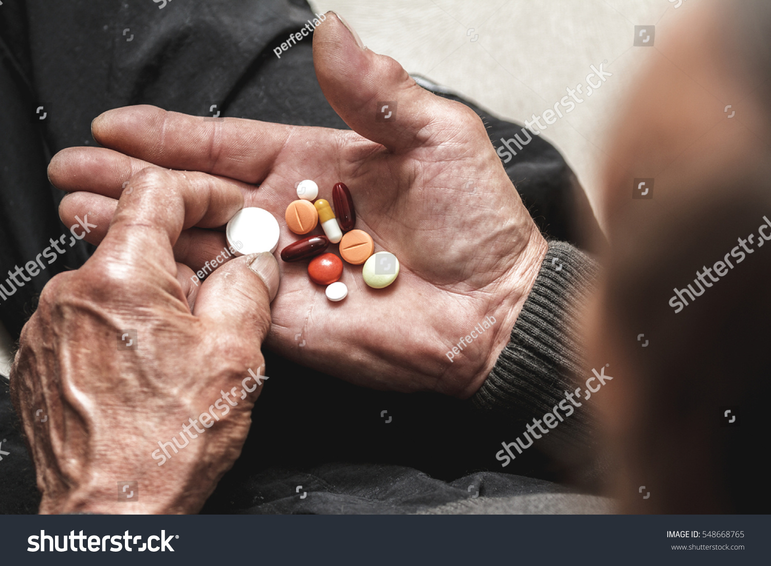 Many multi-colored pills in a Senior's hands Painful old age Caring for the health of the elderly