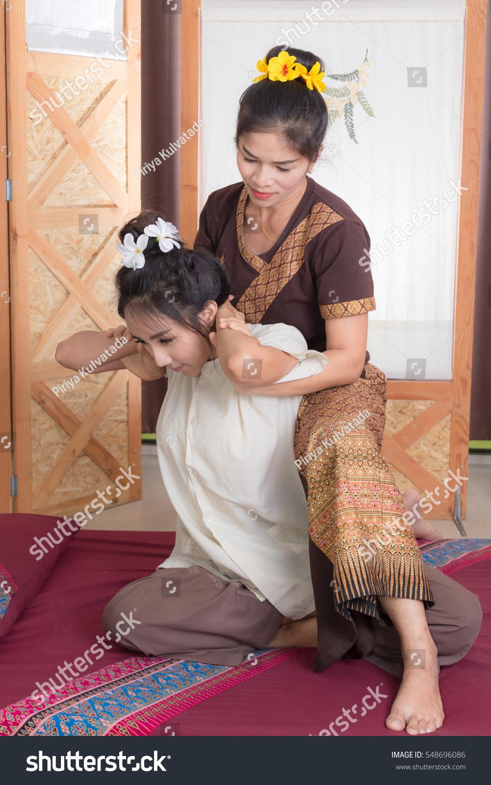Thai massagist doing massage for woman in spa salon. Asian beautiful woman  getting thai herbal