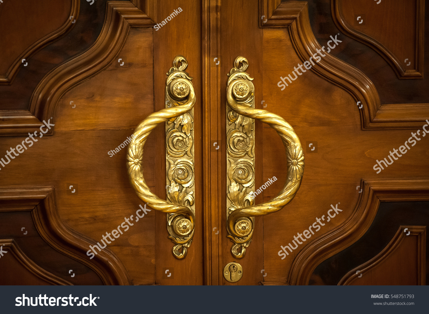 Door handles with an old double door. Golden Handle Door Entrance. Luxury  gold handle - Door Handles Old Double Door Golden Stock Photo 548751793
