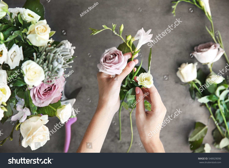 Female florist making beautiful bouquet at flower shop #548929090