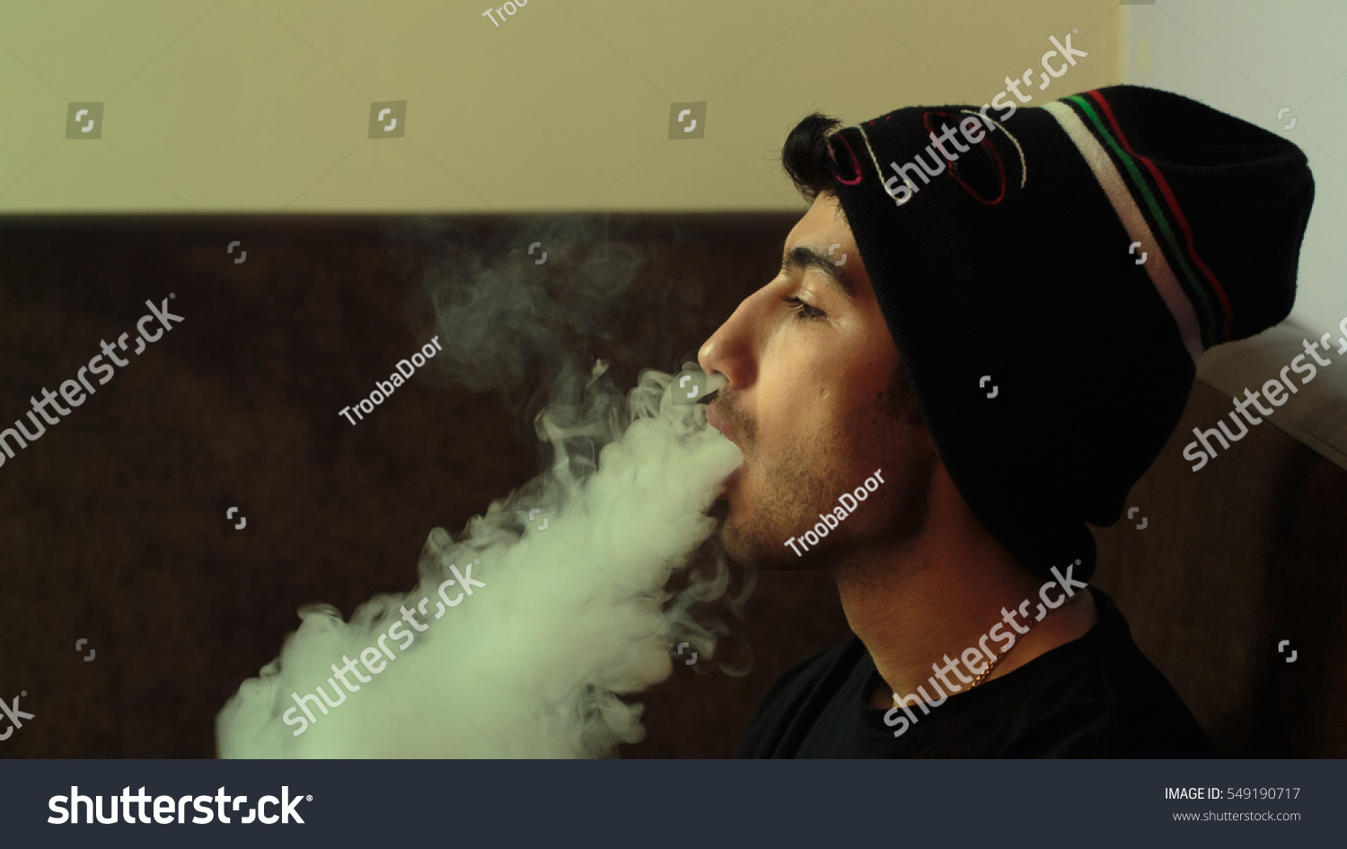 Young handsome guy smoking hookah alone closeup 549190717