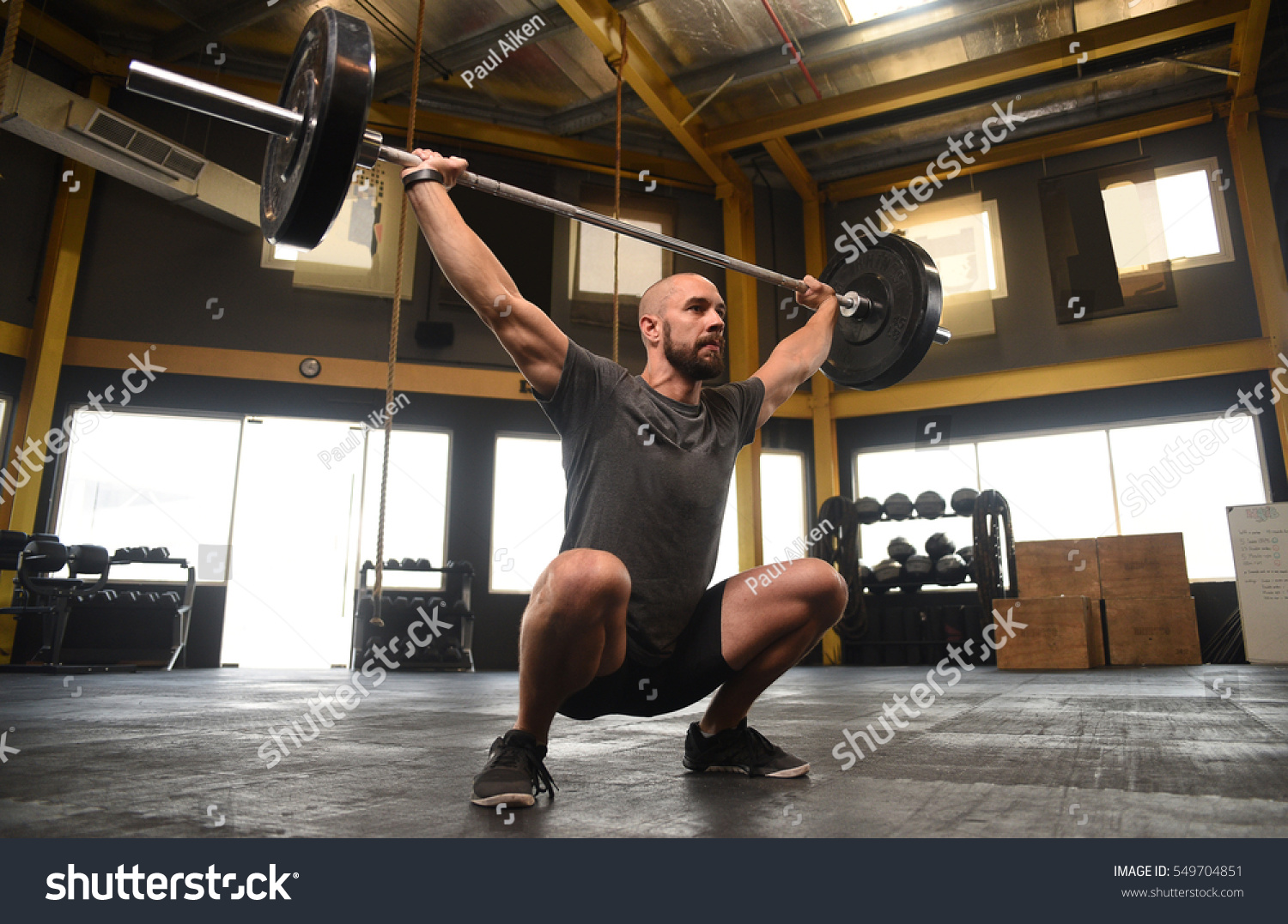Strong crossfit athlete heavy overhead squat stock photo 549704851 strong crossfit athlete in a heavy overhead squat lift in a cross fit box gym platinumwayz