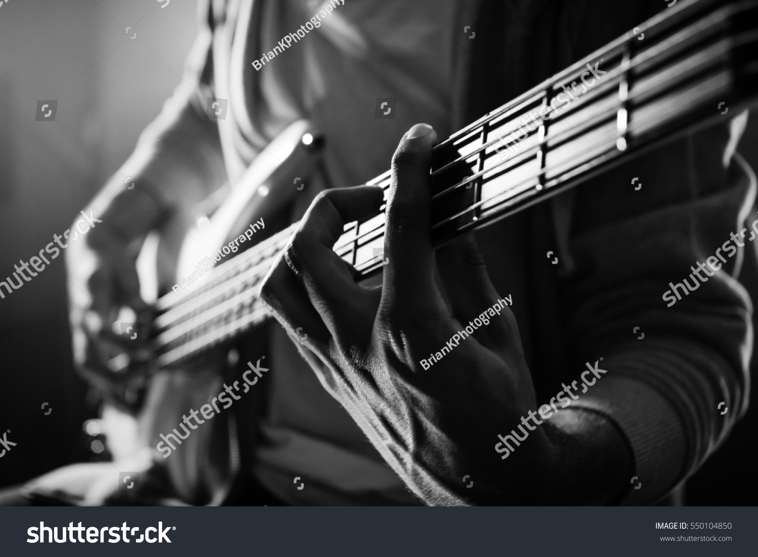Bass Guitarist Playing A Power Chord In Black And White In The Music