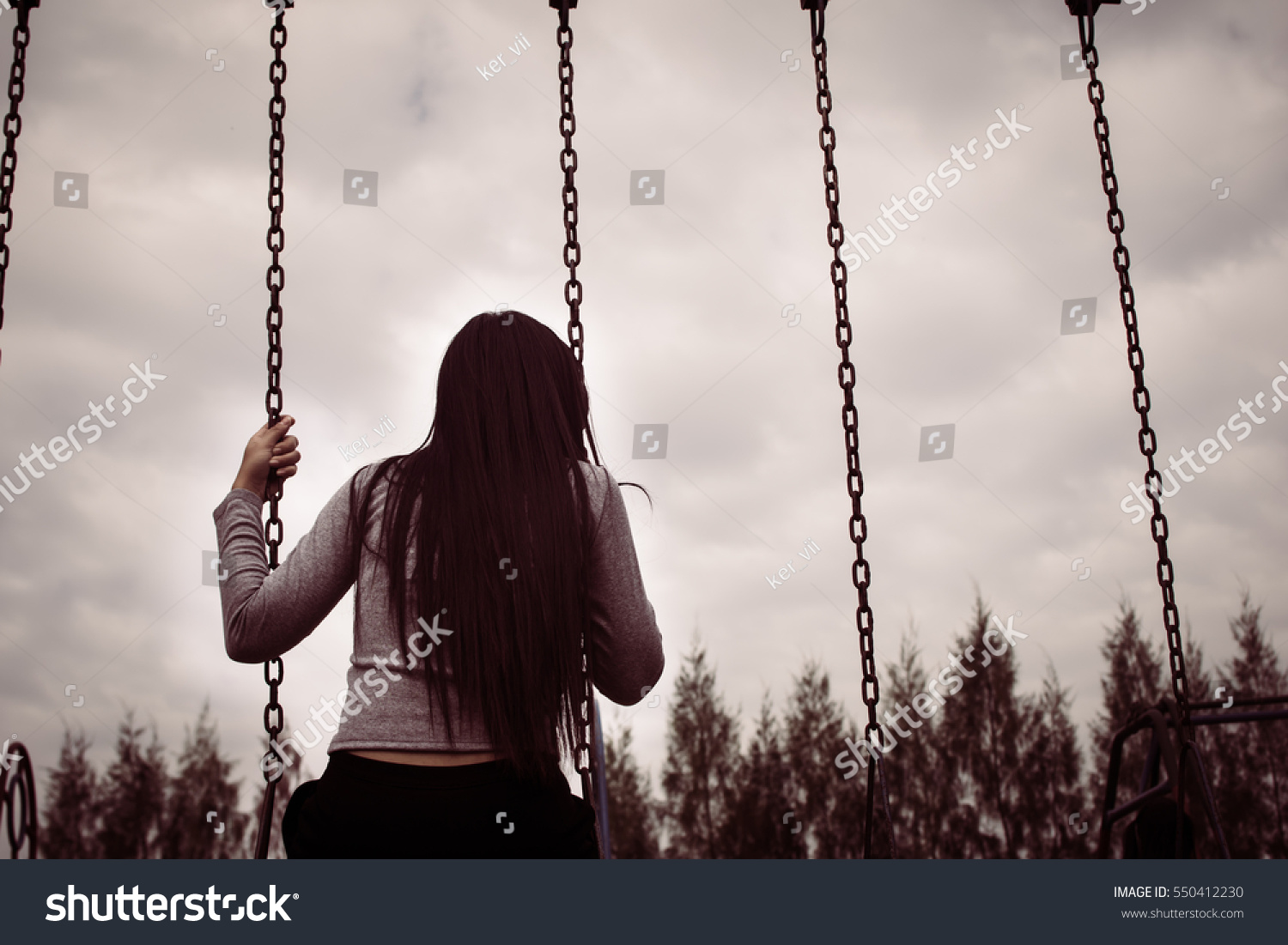 Woman sitting on the swing lonely alone in an empty