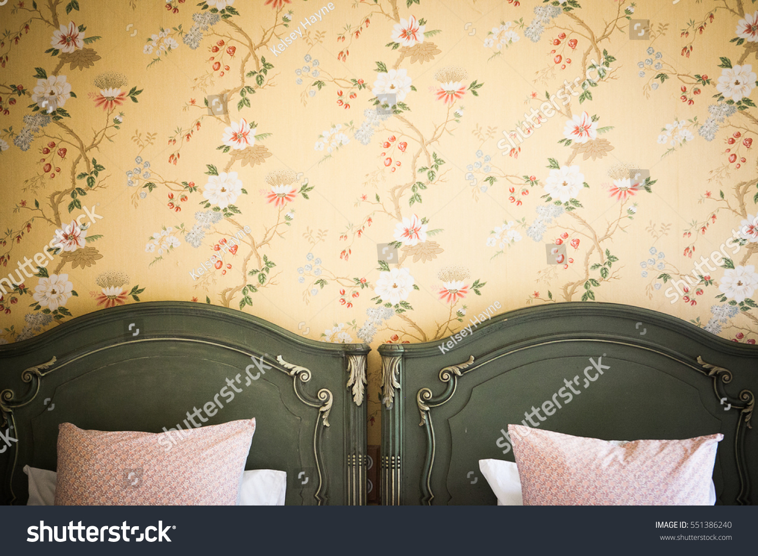 Antique yellow floral french wall paper with green wooden headboards of single beds