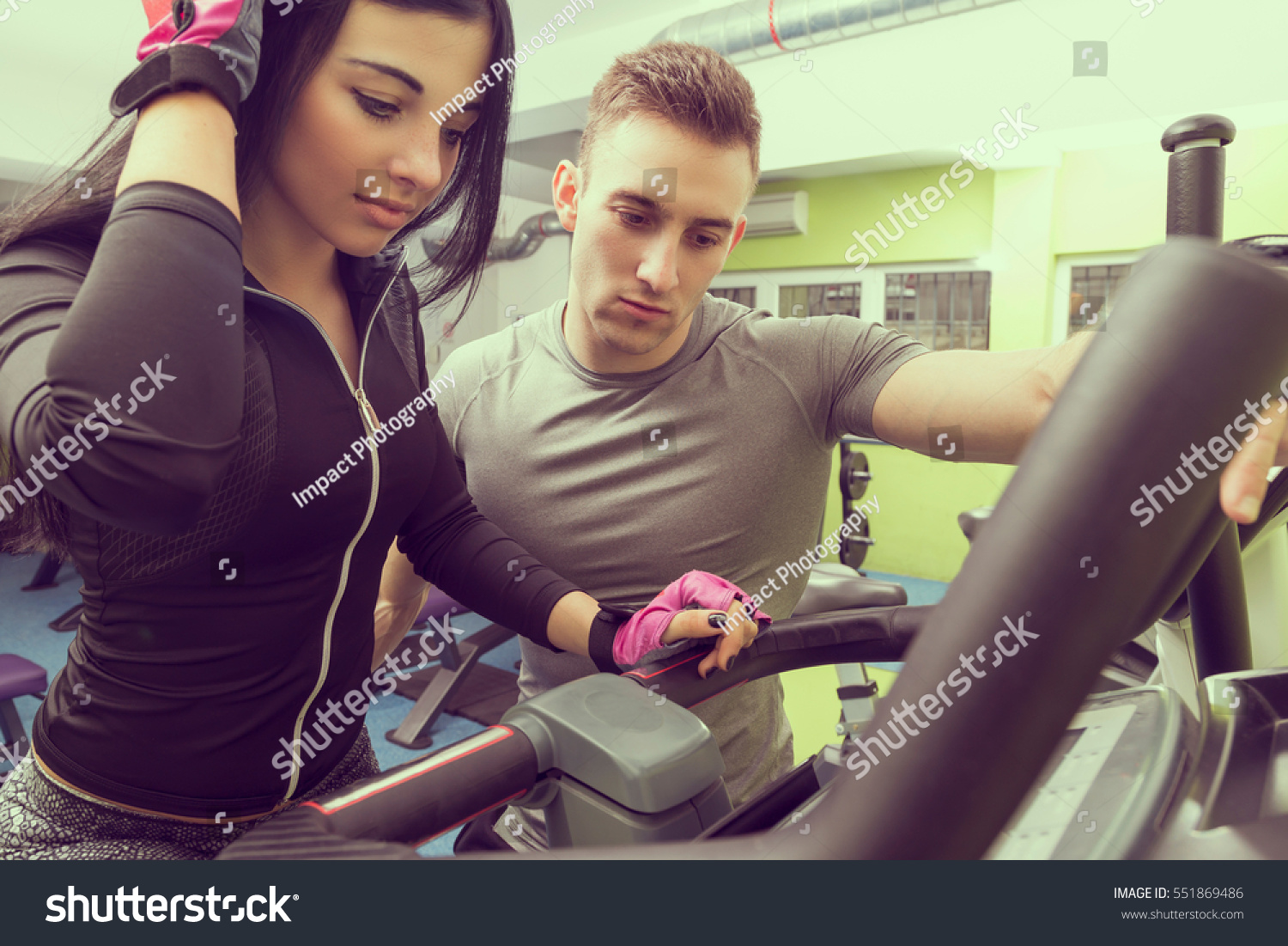 f44421a3898 Personal trainer giving a workout instructions to a female gym client.  Focus on the trainer