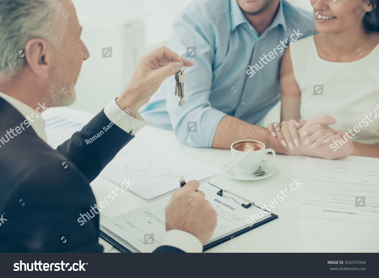 Close up of real estate agent giving keys to couple of customers #552374344