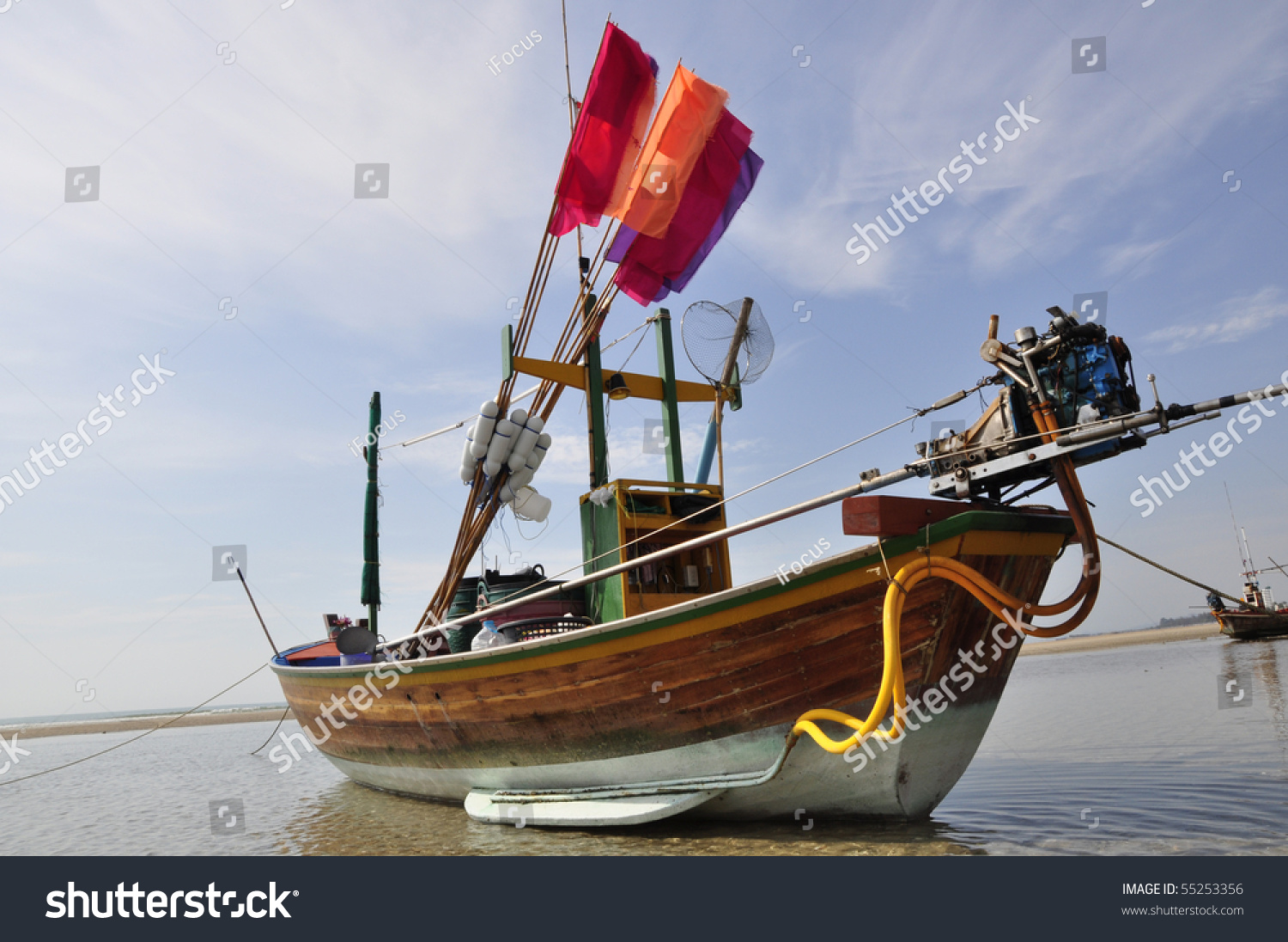Small traditional fishing boat with colorful flags shot on a sunny day in Hua Hin, Thailand