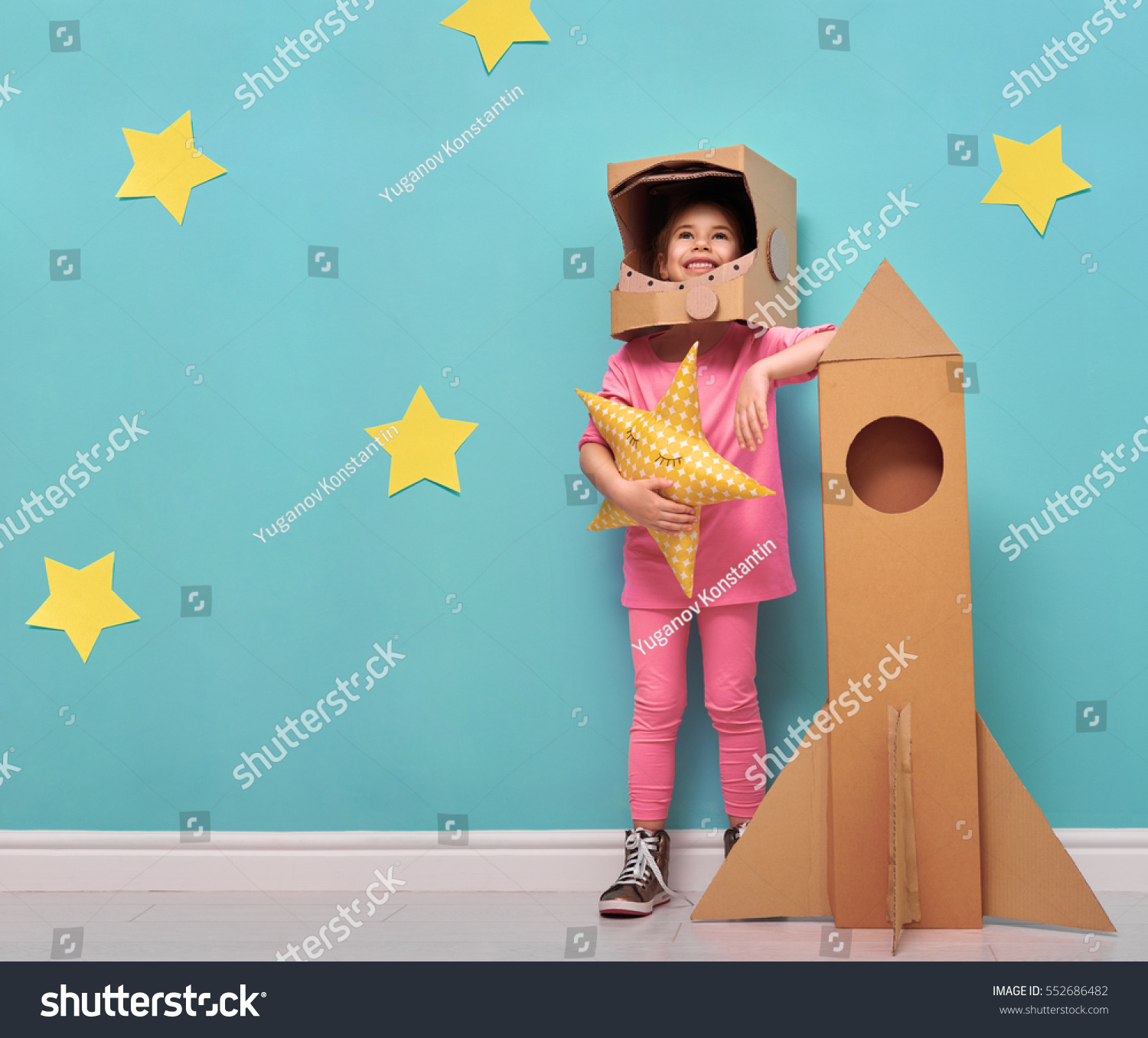 Child girl in an astronaut costume with toy rocket playing and dreaming of be ing a spacemen