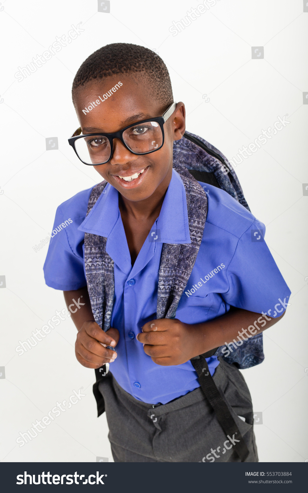 African boy with glasses wearing his school uniform and a rucksack ready to go back to school